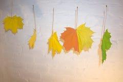 - Hojas amarillas rojas verdes de la caída colgadas en cuerda para tender la ropa con los clips tallados con las letras de un cuc Imagen de archivo