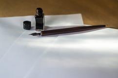 Hojas blancas de la pluma y de la tinta en una tabla de trabajo Imágenes de archivo libres de regalías
