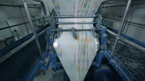 Hojas coloreadas del periódico que mueven encendido un transportador de la tipografía, imprenta almacen de video