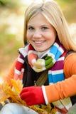 Hojas coloridas sonrientes de la bufanda del otoño de la chica joven Foto de archivo libre de regalías