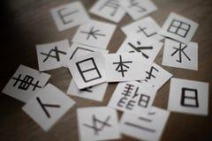 Hojas con mucho kanji de los caracteres de la lengua china y japonesa con la palabra principal Japón imagen de archivo