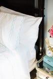 Hojas de cama blancas en cama Fotografía de archivo libre de regalías