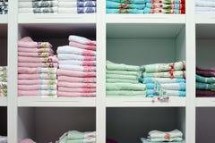 Hojas de cama de las toallas en el estante en una tienda fotos de archivo libres de regalías