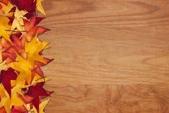 Hojas de la caída en el fondo de madera del grano Fotografía de archivo libre de regalías