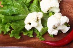 Hojas de la coliflor fresca y de la ensalada verde en el tablero de madera Comida vegetariana Aliste para cocinar Imagenes de archivo