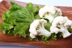 Hojas de la coliflor fresca y de la ensalada verde en el tablero de madera Comida vegetariana Aliste para cocinar Foto de archivo