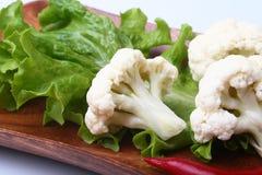 Hojas de la coliflor fresca y de la ensalada verde en el tablero de madera Comida vegetariana Aliste para cocinar Fotos de archivo libres de regalías