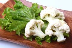Hojas de la coliflor fresca y de la ensalada verde en el tablero de madera Comida vegetariana Aliste para cocinar Fotografía de archivo