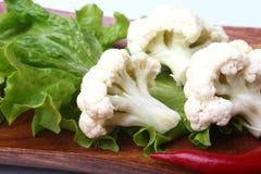 Hojas de la coliflor fresca y de la ensalada verde en el tablero de madera Comida vegetariana Aliste para cocinar Imagen de archivo libre de regalías