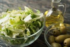 Hojas de la ensalada con la aceituna y el aceite Imagen de archivo libre de regalías