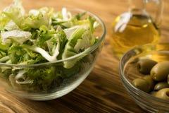 Hojas de la ensalada con las aceitunas y el aceite Imagen de archivo