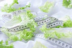 Hojas de la lechuga y cinta métrica en las hojas blancas Foto de archivo