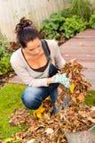 Hojas de la limpieza del otoño de la mujer que cultivan un huerto joven Imagen de archivo libre de regalías