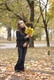 Hojas de la muchacha y del amarillo Fotos de archivo libres de regalías