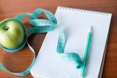 Hojas de operación (planning) de una dieta Un cuaderno c una inscripción - la dieta, cinta métrica, una manzana y pluma foto de archivo