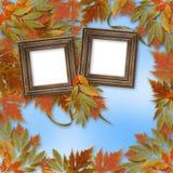 Hojas de otoño brillantes con el marco de madera Imágenes de archivo libres de regalías