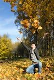 Hojas de otoño de la chica joven que lanzan Imagen de archivo libre de regalías