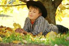Hojas de otoño de la explotación agrícola del niño Imagen de archivo libre de regalías