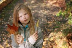 Hojas de otoño de la muchacha que lanzan en el parque Foto de archivo