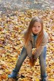 Hojas de otoño de la muchacha que lanzan en el parque Fotos de archivo libres de regalías