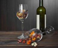 Hojas de otoño en una botella de la copa de vino y de vino en fondo de madera de la tabla Imágenes de archivo libres de regalías