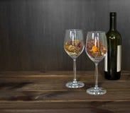 Hojas de otoño en una botella de la copa de vino y de vino en fondo de madera de la tabla Fotos de archivo