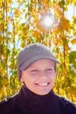 Hojas de otoño felices del brillo del sol de la sonrisa del muchacho del niño Fotos de archivo