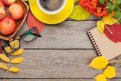 Hojas de otoño, frutas de la manzana, taza de café y libreta imagen de archivo libre de regalías