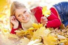 Hojas de otoño de oro, mujer hermosa del pelo rubio Imagen de archivo