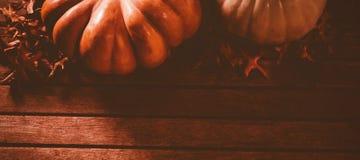 Hojas de otoño por las calabazas en la tabla de madera Imagen de archivo libre de regalías