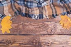 Hojas de otoño y tela escocesa a cuadros en fondo de madera rústico Foto de archivo
