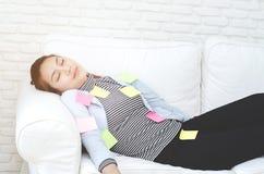Hojas de papel amarillas, verdes y rosadas en la mujer que está durmiendo y agotado de trabajo foto de archivo