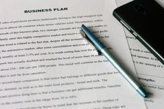 Hojas de papel blancas con el texto impreso en la tabla con una pluma azul y un smartphone negro Auditar estados financieros fotos de archivo libres de regalías