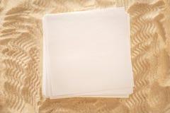 Hojas de papel en blanco en la arena Fotografía de archivo