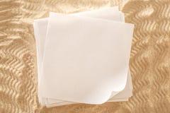 Hojas de papel en blanco en la arena Foto de archivo libre de regalías