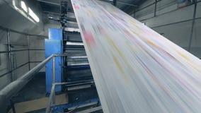 Hojas de papel largas que mueven encendido una línea en una oficina de la impresión, equipo de la fábrica en trabajo almacen de metraje de vídeo