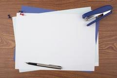 Hojas de papel y accesorios de la oficina en textura de madera Imagen de archivo