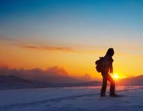 Hojas de ruta (traveler) de la mujer que van de excursión en montañas del invierno Foto de archivo libre de regalías