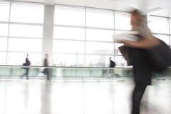 Hojas de ruta (traveler) ocupadas que acometen a través de un aeropuerto Imágenes de archivo libres de regalías