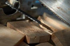 Hojas de sierra del rompecabezas y de la mano sobre ladrillos de madera imagen de archivo