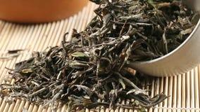 Hojas de té blancas secadas, crudas en taza de té en la cacerola de bambú de la cámara de la estera almacen de video