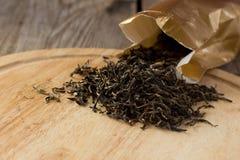 Hojas de té blancas secas en la placa de madera Fotos de archivo libres de regalías
