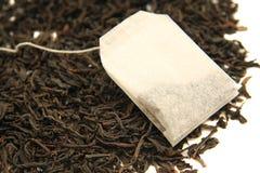 Hojas de té con la bolsita de té Foto de archivo libre de regalías