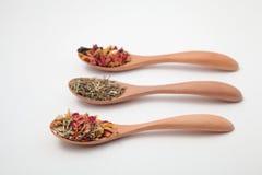 Hojas de té herbarias de la mezcla en cucharas de madera Imagen de archivo