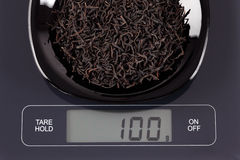 Hojas de té negras en escala de la cocina Fotografía de archivo