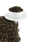 Hojas de té negras en una taza Fotografía de archivo libre de regalías
