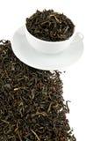 Hojas de té negras en una taza Foto de archivo libre de regalías
