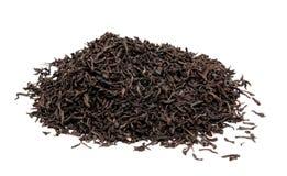 Hojas de té negras secas aisladas en un blanco Imágenes de archivo libres de regalías