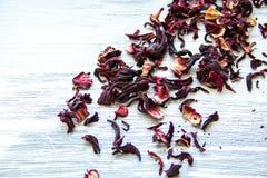 Hojas de té rojas secas en fondo de madera imagen de archivo
