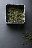 Hojas de té verdes en caja Imágenes de archivo libres de regalías